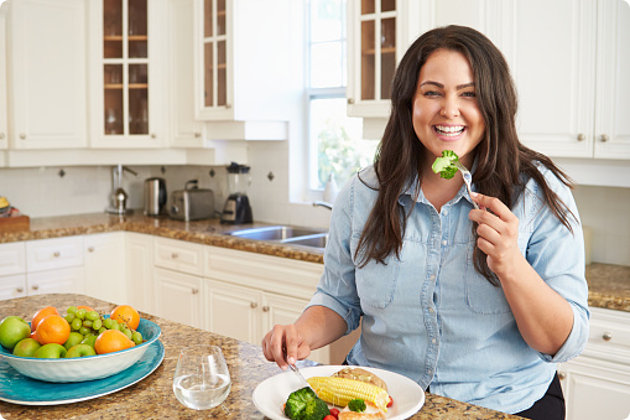 Woman Eating Healthy Meal In Kitchen