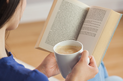 Women reading a book with a cup of coffee