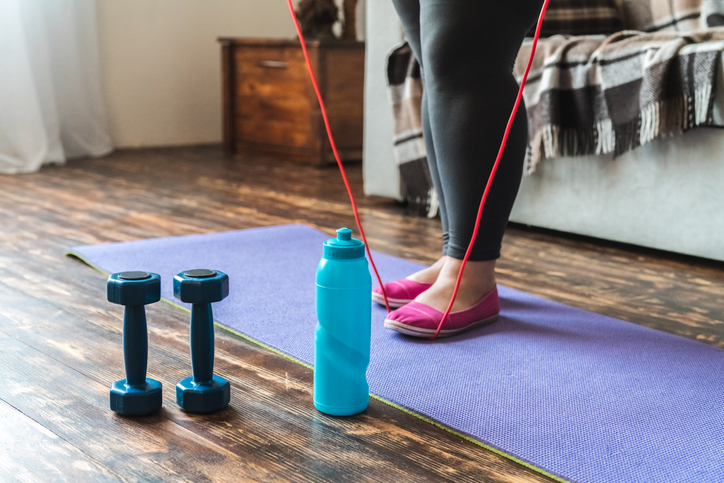 Woman at home standing on yoga mat legs close-up holding jump rope
